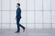 Young business man with suit and defocused face walking in street on a white wall background.