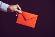 赤い色の手紙を持っている男性の手