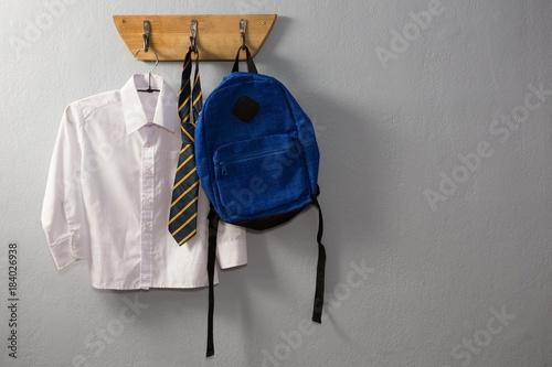 Fotomural  School uniform and schoolbag hanging on hook