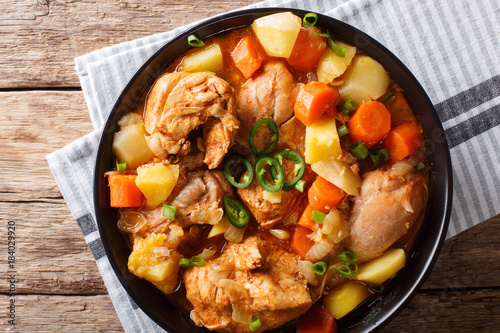 Photo Stands Ready meals Spicy stewed chicken with vegetables close-up in a bowl. Horizontal top view