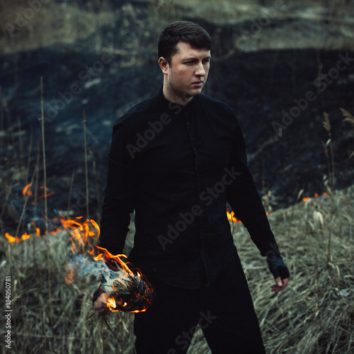 Photo handsome man with a torch in his hands sets fire to the grass in the field