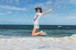 Happy free young sexy woman in sunglasses jumping on the beach of tropical island of Bali.