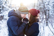 Young lovely couple warming up each others hands in snowy winter forest park. New Year, Christmas and winter clothes sale concept