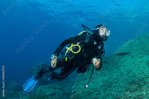 Fotografia woman scuba diving over rocks in the Mediterranean Sea
