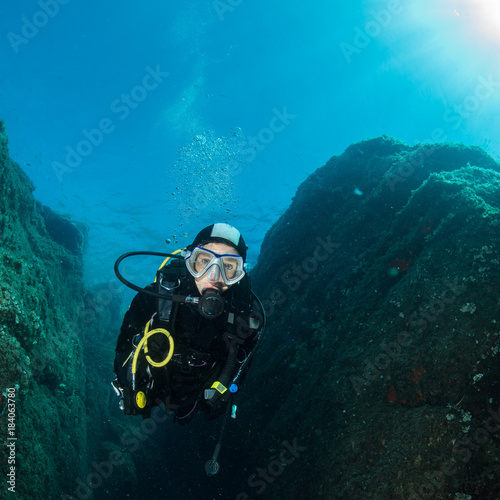 Canvas Prints Diving woman scuba diving over rocks in the Mediterranean Sea