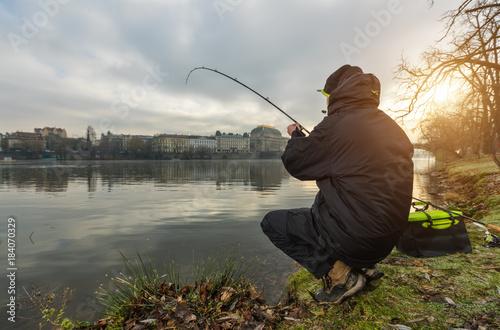 Sport fisherman trying to catch fish in river, urban fishing.