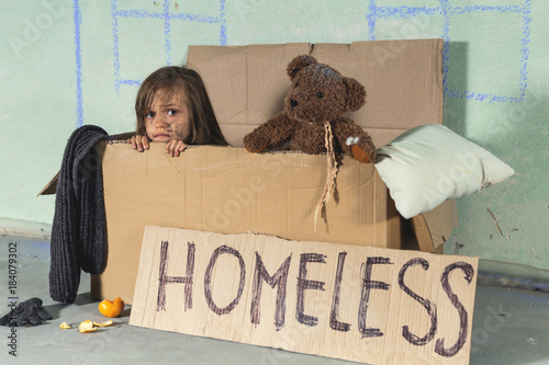 Obraz na plátně Depressed homeless kid girl living in the cardboard and looking at camera