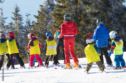Ski instructor teaching young kids to skiing