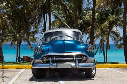 amerykanski-niebieski-chevrolet-klasyczny-samochod-zaparkowany-na-plazy-pod-p