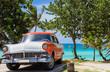 Amerikanischer orange weisser Ford Fairlane Oldtimer parkt direkt am Strand unter Palmen in Varadero Cuba - Serie Cuba Reportage