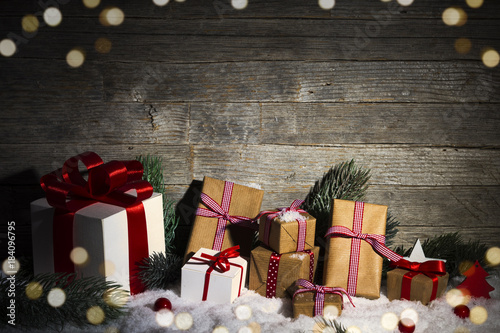 christmas gifts and onrmanents on snow old wooden background
