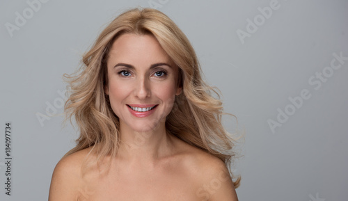 Cadres-photo bureau Spa Beauty concept. Portrait of happy attractive middle-aged woman is standing with naked shoulders and looking at camera with wide smile. Isolated background with copy space in the right side