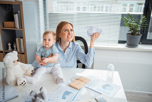 Fotografia, Obraz  Portrait of angry businesswoman crumpling paper while holding serene kid in hand