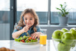 Portrait of pretty little female child having healthy breakfast. She is holding fork under the chopped vegetables and smiling