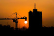 Scene of silhouette dusk construction site, crane with skyscraper over sunset background.