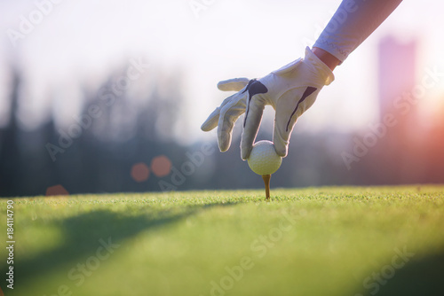 Fotografía  Golf ball gentle put lie on the wooden tees by hand of woman golf player, before