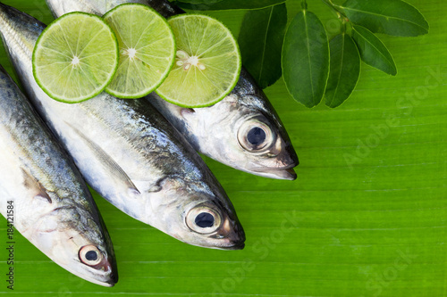 Fotografija fish with lemon and leafs on banana leaves background,concept cooking background