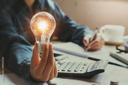 new idea and creative concept for business woman hand holding light bulb in office