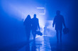silhouette of people walking in a tunnel in smoke against a background of bright light. mysterious mood