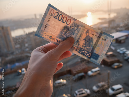 Poster New russian 2000 rubles in hand over city background.