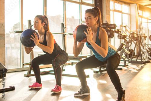 dwie-dziewczyny-sportowe-robienie-cwiczen-z-pilkami-fitness-na-silowni
