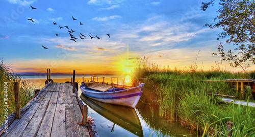 Fotografering  puesta de sol sobre el embarcadero del lago