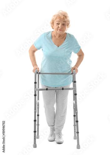 Photo  Elderly woman with walking frame on white background