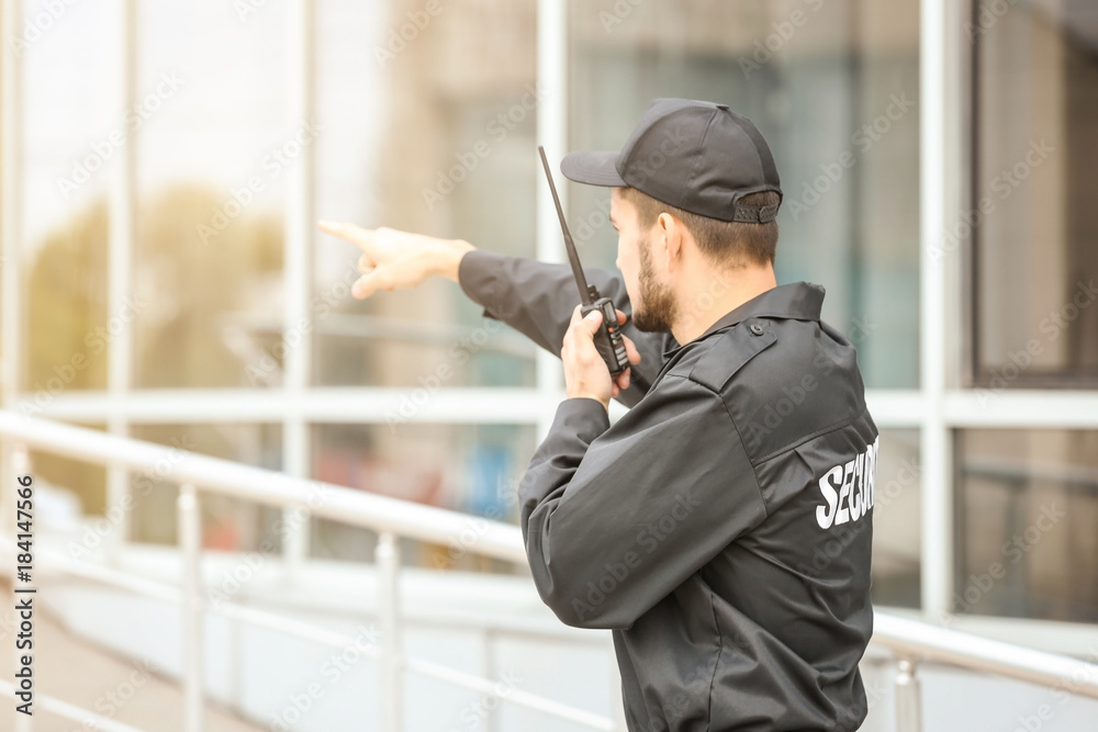 Fototapeta Male security guard using portable radio transmitter near building outdoors