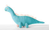 Cute toy dinosaur on table against white background