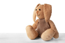 Cute Toy Bunny On Table Against White Background