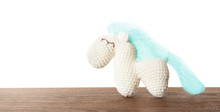 Cute Knitted Toy Horse On Table Against White Background