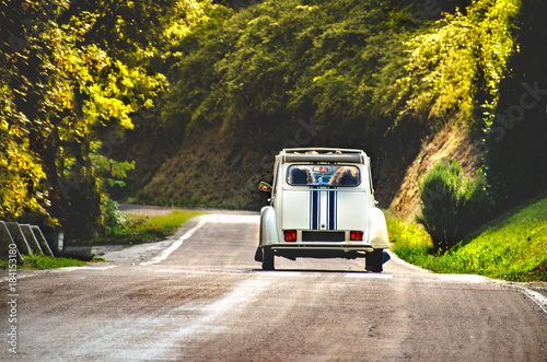 Keuken foto achterwand Vintage cars vintage car country winding road back view friends road trip