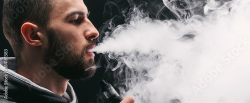 Canvastavla Young man vaping e-cigarette with smoke on black