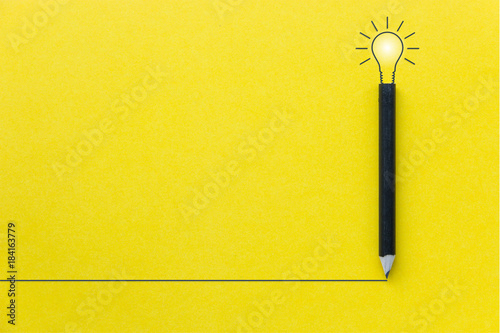 Fotografia  Black pencil on yellow backgroud with light bulb illustration line and copyspace