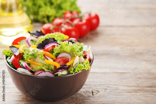 Vegetable salad in bowl on grey wooden table Canvas Print