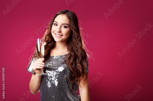 Fototapeta Young woman with glass of champagne on pink background obraz na płótnie
