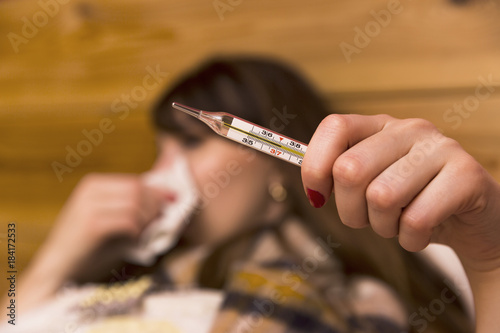 Fotografia  Sick woman in her bed looking at a clinical thermometer