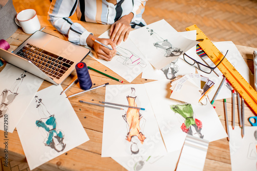 Fotografija Fasion designer sketching clothes drawings at the table with tailoring tools and
