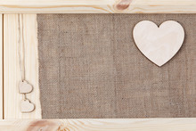 Heart On A Wooden Background Covered With Burlap, A Card For Valentine's Day.
