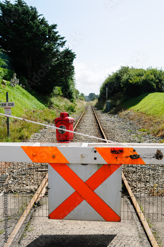 Fotografia, Obraz  Manually operated level crossing barrier with paraffin warning lamp light across