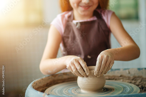 Fototapeta Hands of young potter, close up hands made cup on pottery wheel