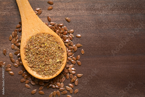 Fotomural  Ground or crushed brown flax seed or linseed on wooden spoon, photographed on da