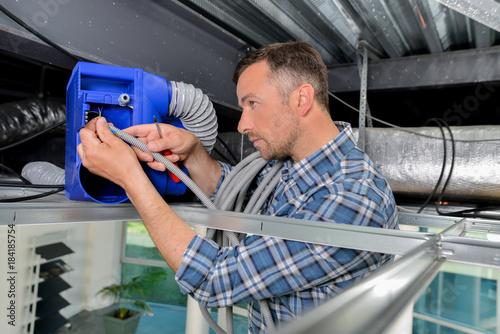 Man repairing ceiling ventilation Wallpaper Mural