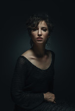 Portrait In Low Key Beautiful Adult Woman Sitting On A Chair Wearing A Knitted Dress Emotional Portrait