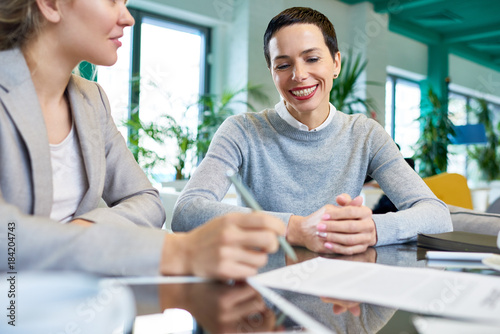 Fototapeta Portrait of mature businesswoman with short dark hair smiling happily while talking to partners during meeting in office obraz na płótnie