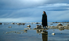 Woman In A Raincoat Walks Alon...