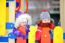 Little Boy And Girl In Winter Clothes Having Fun In Outdoors Playground