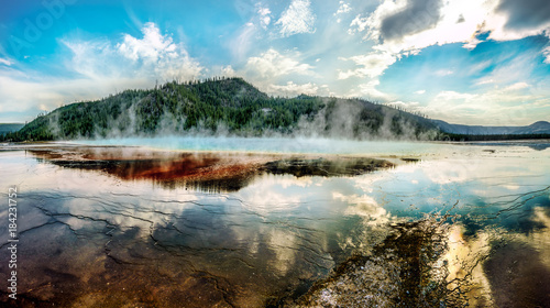 Midway Geyser Basin, The Grand Prismatic Spring. Golden Yellowstone National Park, USA. This effect was possible thanks to colorful bacteria living in a very mineral-rich warm water around the source