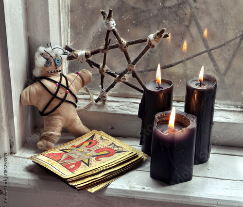 Voodoo doll, tarot cards, pentagram and black candles by old window. Occult, esoteric, divination and wicca concept, mystic background
