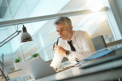 Fotomural  Businessman working on laptop in office, being concerned